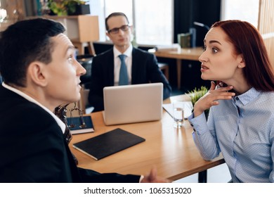 Redheaded angry woman argues with adult man in divorce lawyer's office. Adult couple gets divorced from attorney for divorce in office.