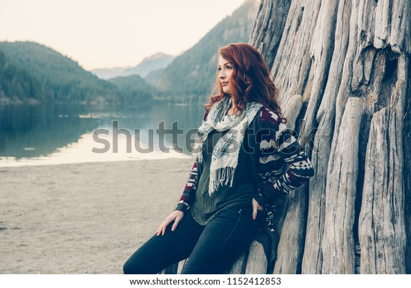 Red-Headed Caucasian Woman At The Lake During Fall. Pacific Northwest Theme. British Columbia, Washington, Idaho or Montana