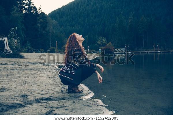 Red-Headed Caucasian Woman At The Lake During Fall. Pacific Northwest Theme. British Columbia, Washington, Idaho or Montana