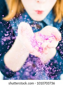 Redheaded child blowing hot pink glitter from hands