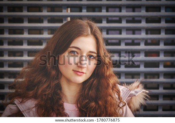 Redheaded girl looks at the camera with a calm expression on her tender fresh face, pulling down her chin a little bit, posing in front of metal grid, shot with copyspace