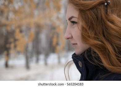 The redheaded girl looks into the distance in autumn forest