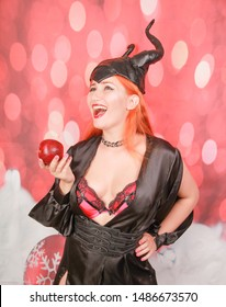 redheaded girl in sexy black dress with devil horns holds red apple with temptation and seduction