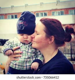 Redheaded mother with calm smiling face embracing cute baby on the street.