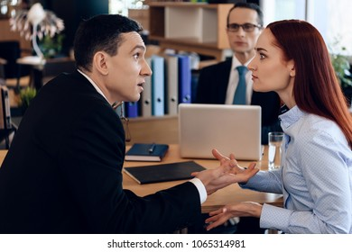 Redheaded woman argues with adult man in divorce lawyer's office. Adult couple gets divorced from attorney for divorce in office.