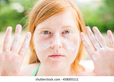 Redheaded woman with freckles holding her hands in front of her sunscreen covered face.  She also has sunblock on her hands.