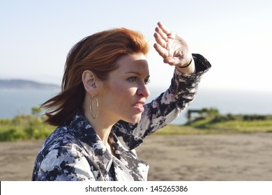 Redheaded woman shielding her eyes from the sunlight
