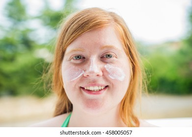 Redheaded woman smiling while her face is covered in sunscreen.