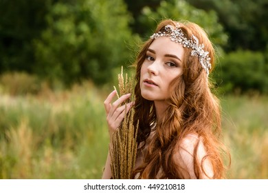 Redheaded young girl in the woods. Portrait of the bride in the Park. A girl holds wheat ears in the hands.