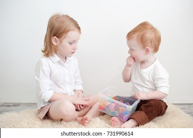 Redheads brother and sister play in the children's room