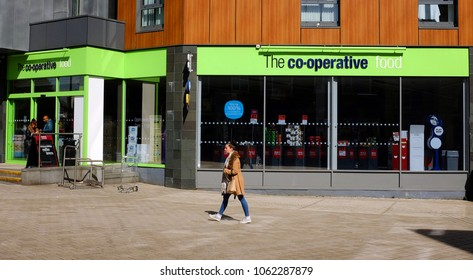 REDHILL, UNITED KINGDOM - APRIL 5 2018:  A woman walks past a branch of food retailer Co-operative (Co-op) Food, which is a network operated operated by over 15 co-operative societies in the UK.