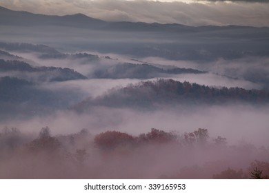 red-hued fog draping smoky mountains at sunrise