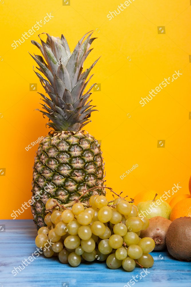 Pineapple, grapes and other fruits on yellow background. Various fruits