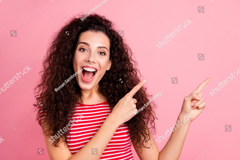 Close-up portrait of her she nice-looking attractive charming cute adorable shine cheerful cheery wavy-haired girl pointing aside isolated over pink pastel background