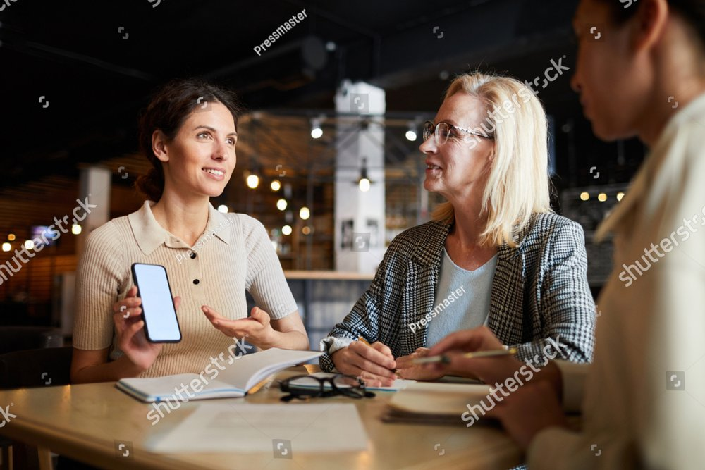 One of contemporary employees showing her colleagues curious promo in her mobile gadget and consulting about the goods or discount