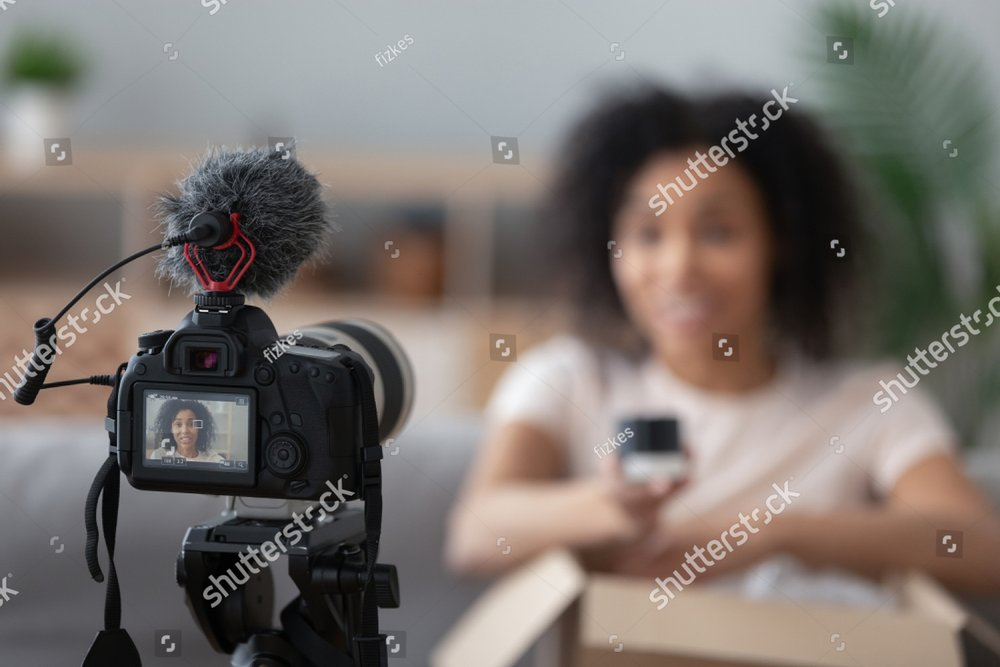 Professional camera device shooting african American young woman blogger making unpacking video at home, black biracial young woman vlogger influencer record content on cam, brand advertising promo