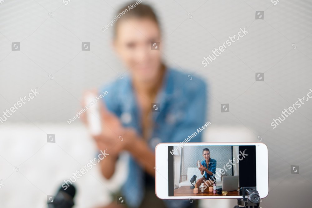 close up of smart phone screen with video broardcasting of makeup artist youtuber influencer broadcasting demonstrating cosmetic products live online