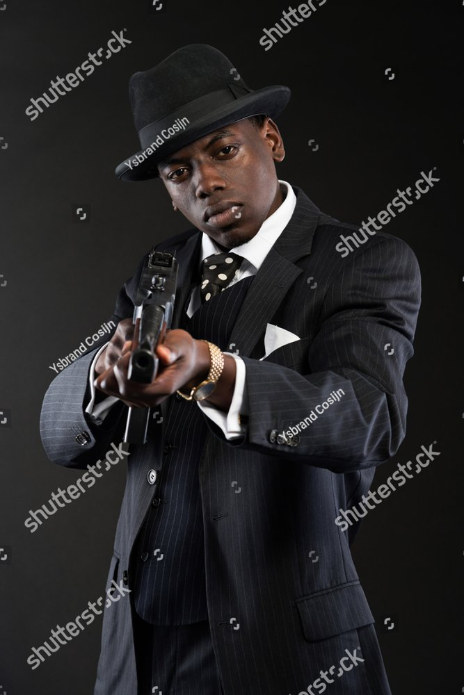 Retro african american mafia man wearing striped suit and tie and black hat.  Shooting with machine gun. Studio shot. fcded92a6f06