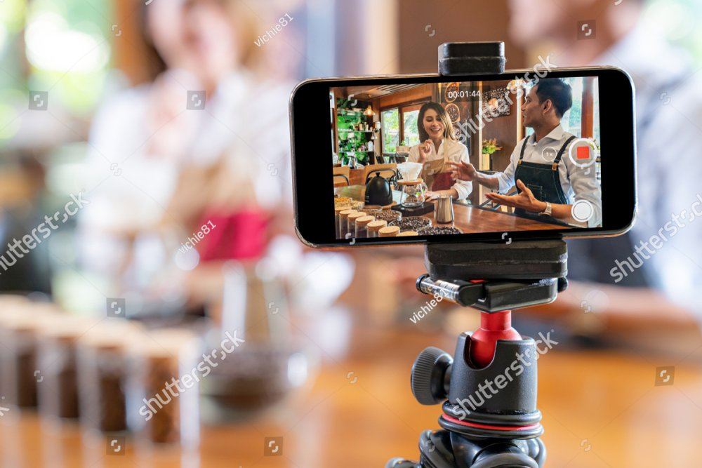 VLOG of  young adult asian owner entrepreneur review cafe coffee shop and live in social media for online marketing with smart phone in cafe. Startup of small business marketing consumerism concept
