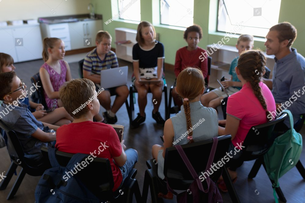 High angle view of a diverse group of elementary school kids sitting on chairs in a circle and interacting during a lesson, their Caucasian male teacher sitting with them and talking