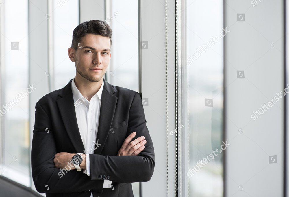 Handsome young businessman with folded arms in the office. Cheerful self confident man with crossed hands portrait. Business, success, people, office lyfestyle concept