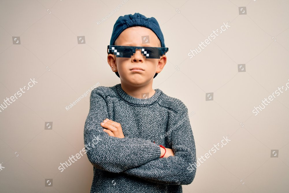 Young little caucasian kid wearing internet meme thug life glasses over isolated background skeptic and nervous, disapproving expression on face with crossed arms. Negative person.