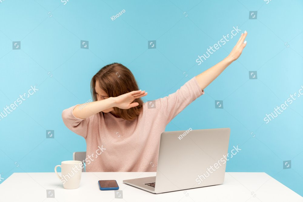 Dabbing trends. Overjoyed woman showing dab dance gesture, performing internet meme of success, sitting at workplace with laptop, home office job. indoor studio shot isolated on blue background