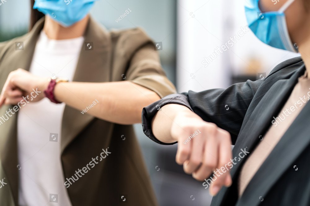 Close up two businesswomen do alternative greeting in new normal office lifestyle. They wear protective face mask and use elbow bump instead of handshake to reduce infection of coronavirus COVID-19.