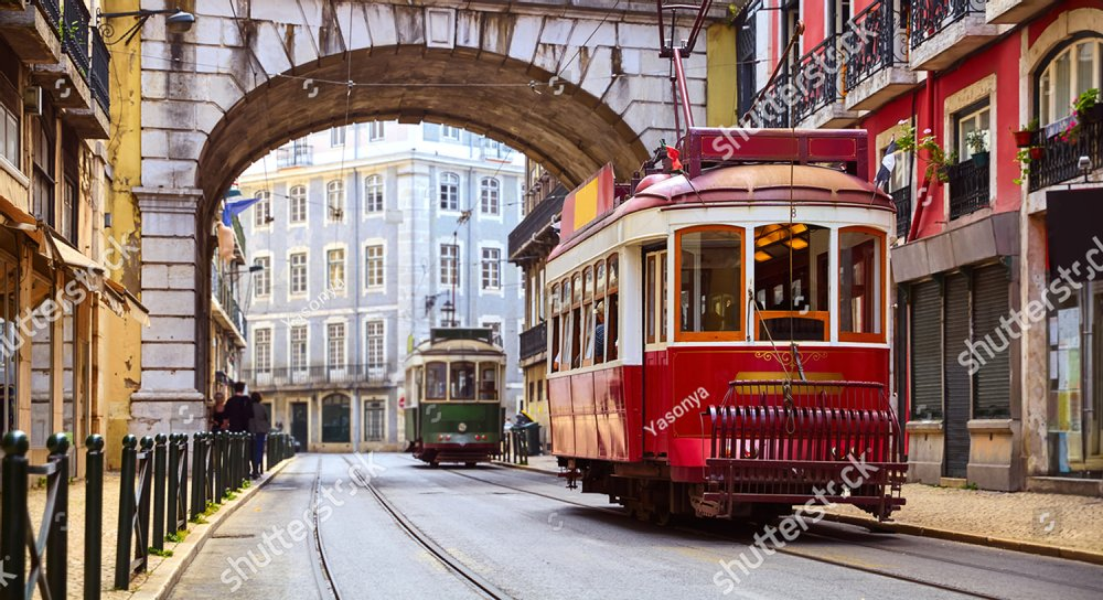 Lisbon, Portugal. Vintage red retro tram on narrow bystreet tramline in Alfama district of old town. Popular touristic attraction of Lisboa city. Public tramways trasport.