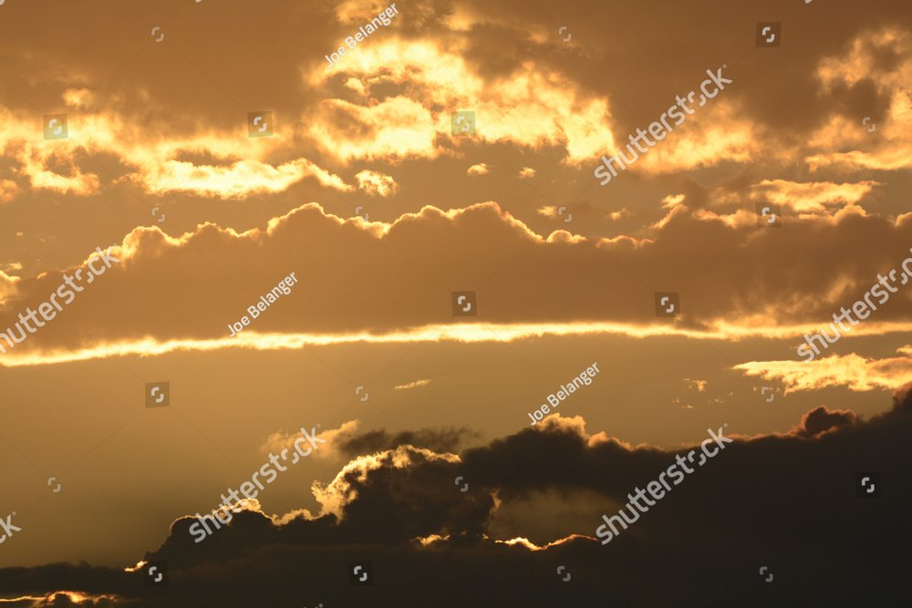 Beautiful yet moody sunrise with storm clouds in the lower thirds and reflective golden light bouncing off of the other clouds.