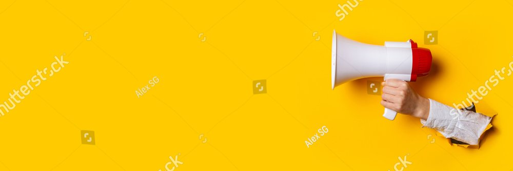 Hand holds a megaphone from a hole in the wall on a yellow background. Concept of hiring, advertising something. Banner.