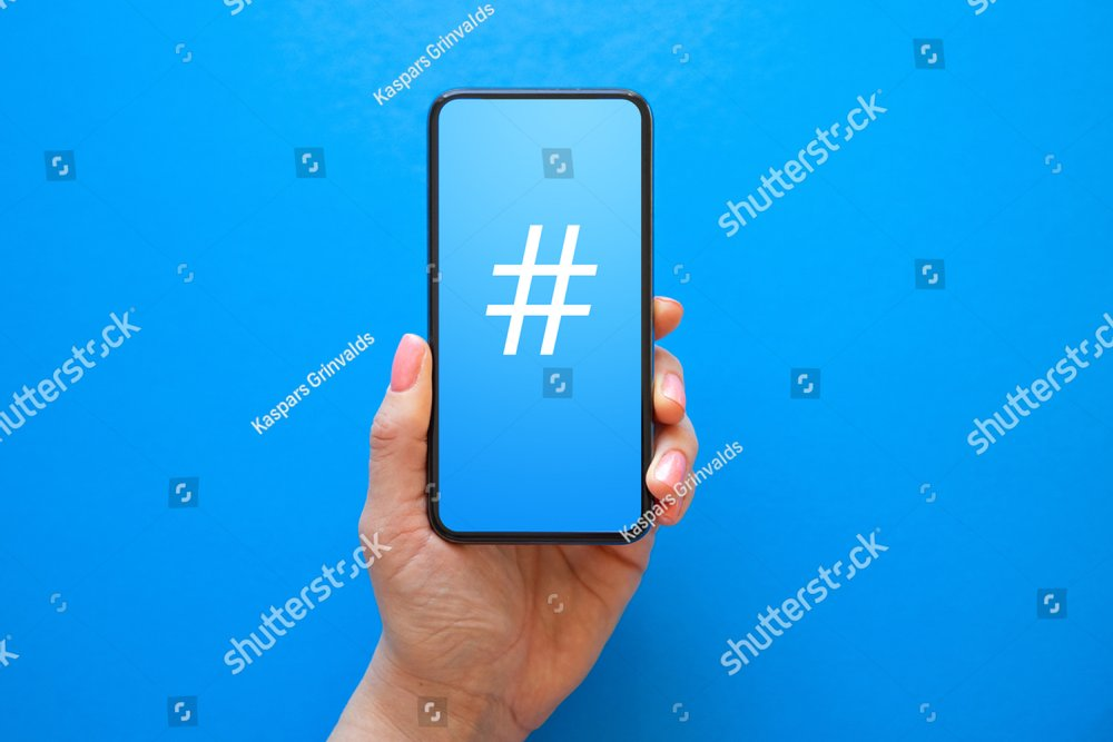 Person holding mobile phone with hashtag symbol on the screen