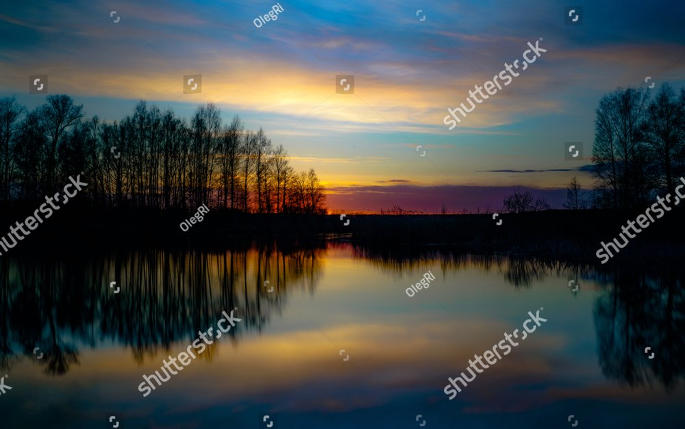 sunset at coast of the lake. Nature landscape. Nature in northern Europe. reflection, blue sky and yellow sunlight. landscape during sunset.