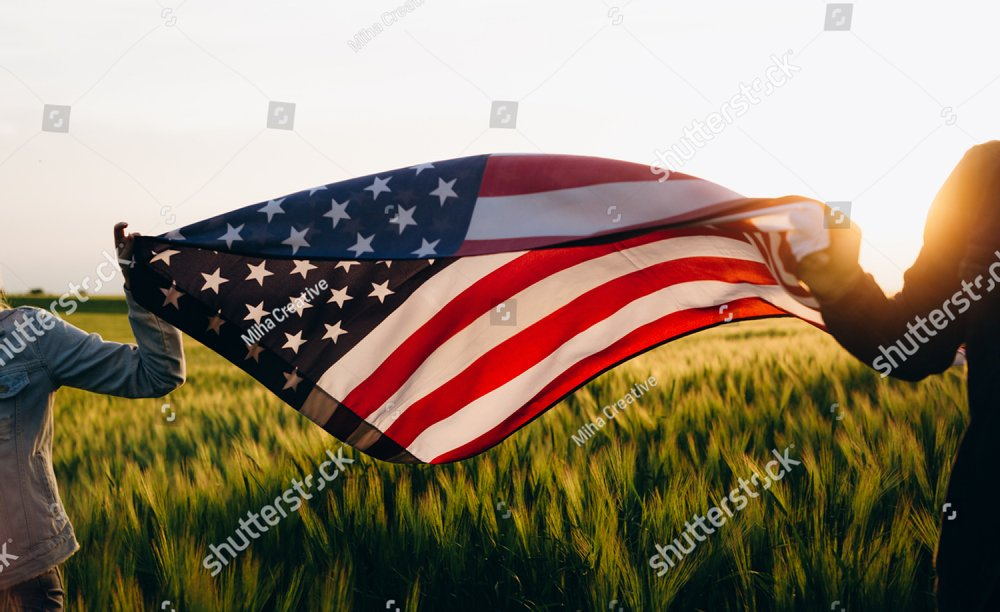 4th of july Patriotic holiday. Independence day. Hands holding american flag at sunse.