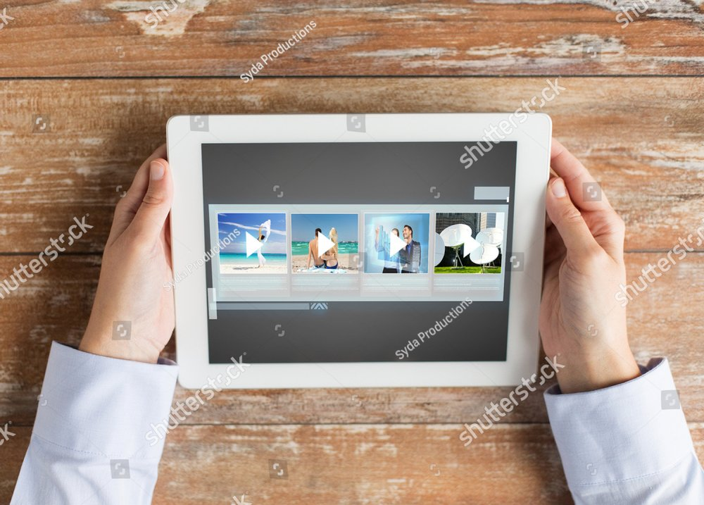 people, multimedia and technology concept - close up of hands with video gallery slideshow on tablet pc at table