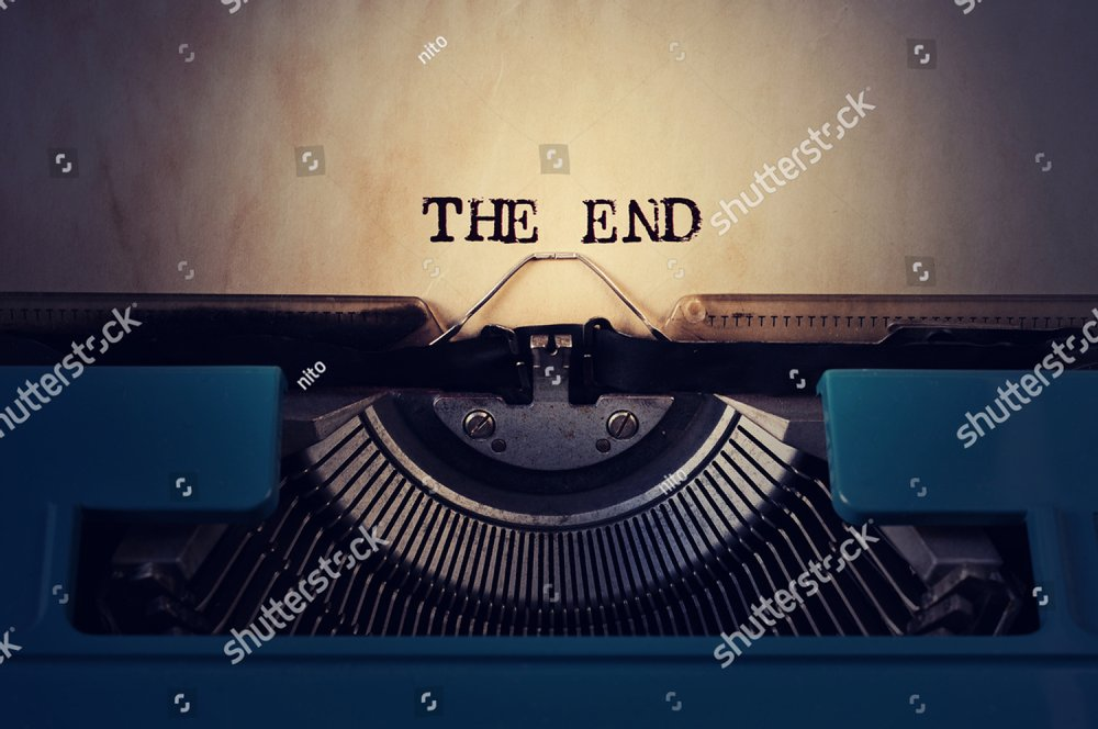 closeup of a blue retro typewriter and the text the end written with it in a yellowish foil