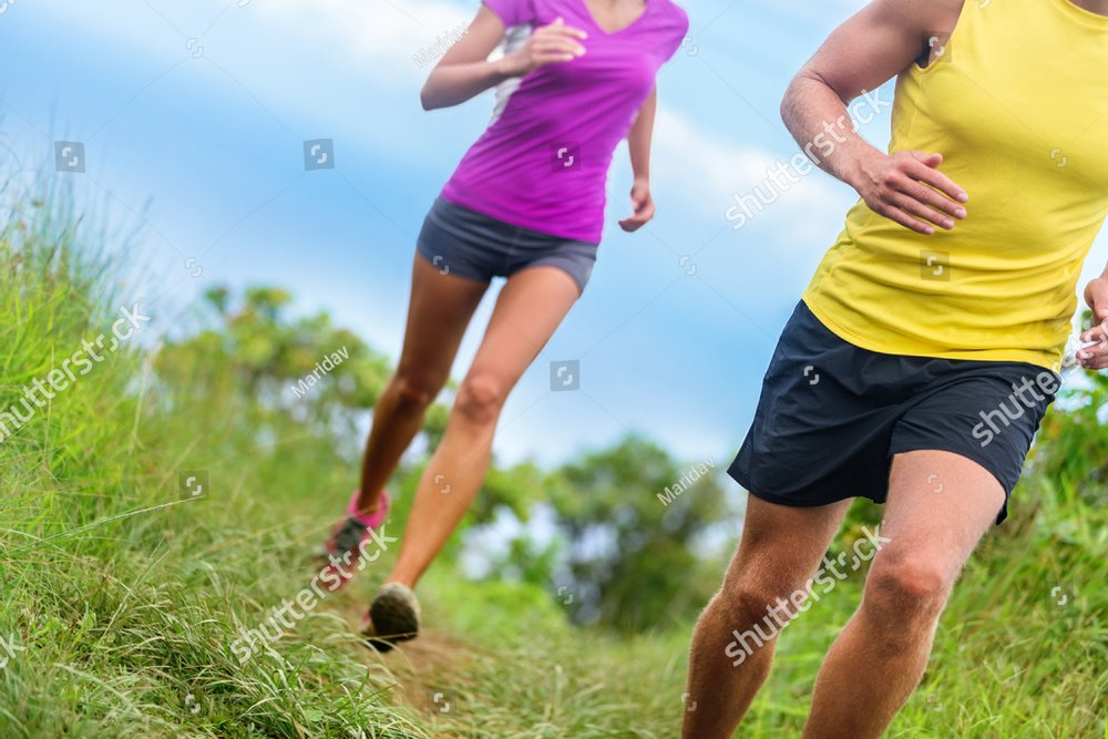 Fitness athletes trail running - athletic legs closeup lower body crop of man and woman working out. Sports people jogging in fast motion marathon race training on a nature path in shorts activewear.