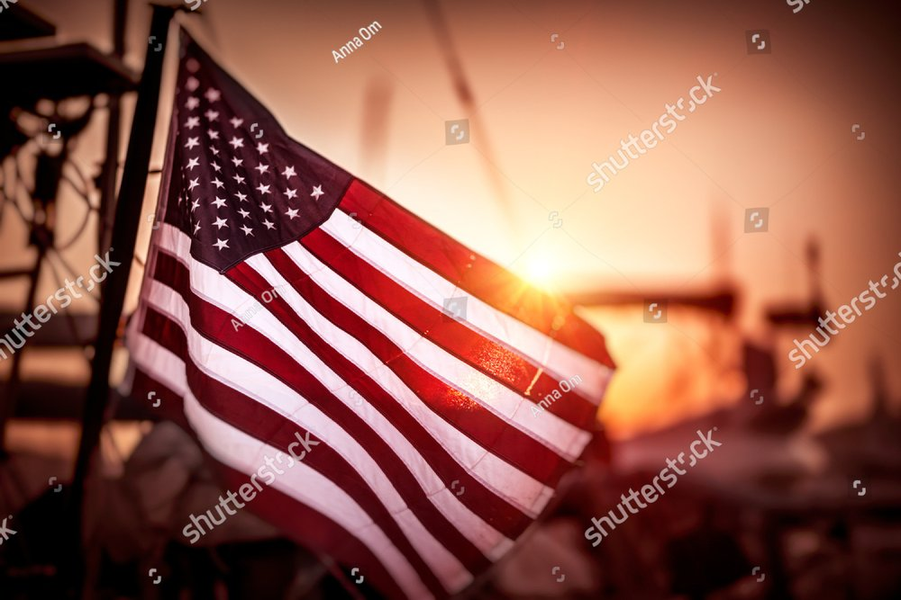Flag of United States of America flutters in the winds in mild sunset light, independence day of America