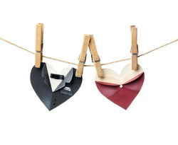 Symbolic male and female heart shapes hanging on the clothesline. Isolated on white. Wedding or st.Valentine theme.