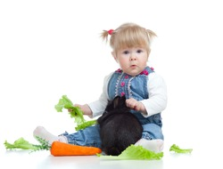 Cute little girl feeding a rabbit with carrot and lettuce on the floor