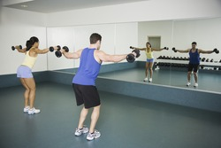 Man and woman lifting weights at gym