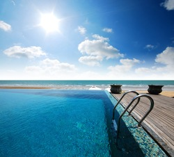 Swimming pool near the beach at high class resort in thailand for relax relaxation beautiful sea sand sun blue sky in Thailand