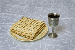 plate of passover matzo with kiddush cup of wine; photographed on light table cloth.