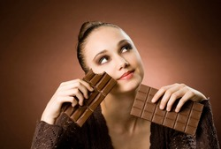 Portrait of a striking brunette beauty enjoying chocolate desserts