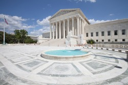 WASHINGTON, DC - AUGUST 20, 2017: A solitary man by the massive steps and pillars at the West Facade of the Supreme Court Building.