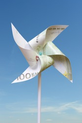 Toy windmill cut from 100 euro banknote over blue sky