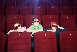 Smiling kids watching cartoons at the cinema