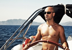 Handsome muscular man at the helm, sailing at Mediterranean sea, traveling the world by sailboat, male model on luxury yacht, water sport vacation, summer outdoors