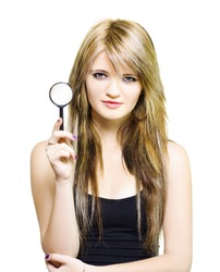 Studio Image Of A Gorgeous Young Woman Holding Magnifying Glass While On A Search To Find Clues And Answer Questions Over White Background