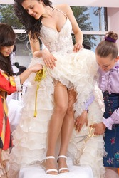Women making adjustment to wedding gown in professional fashion designer studio